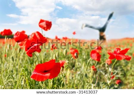 jumping girl in poppy field, focus on poppy - stock photo