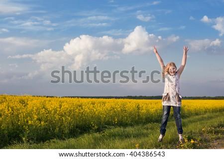 jumping girl in rape field - stock photo
