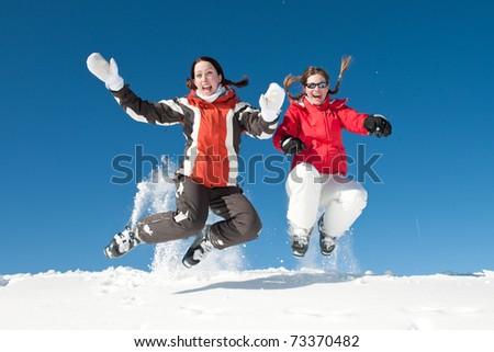 Jumping girls in fresh snow powder - winter fun - stock photo
