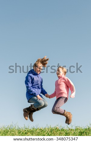 Jumping girls in front of blue sky - stock photo