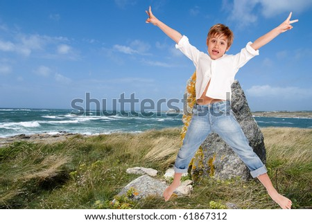 Jumping happy boy in a wild Britton coast - stock photo