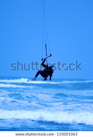Jumping kite surfer of blue background - stock photo