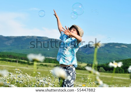 jumping little boy wants to catch soap bubbles - stock photo