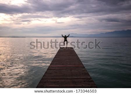 Jumping man celebrating on footbridge in the morning - stock photo