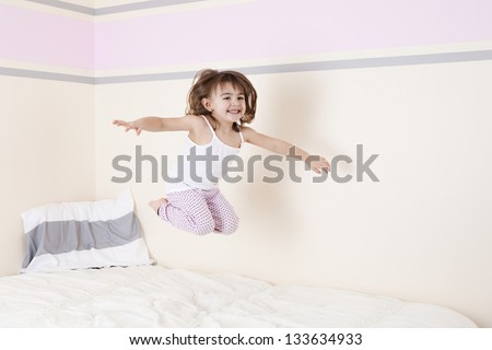 Jumping on the bed.  Room for your text. - stock photo