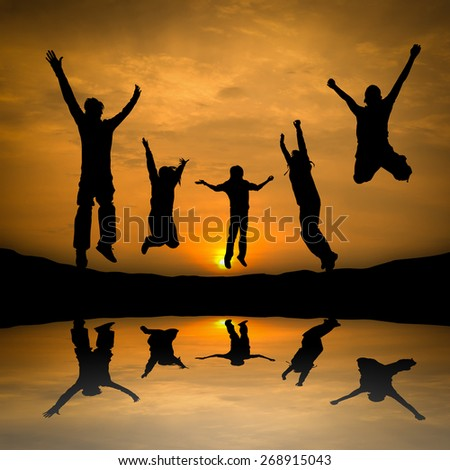 Jumping Silhouette people group team in Sunset time. - stock photo