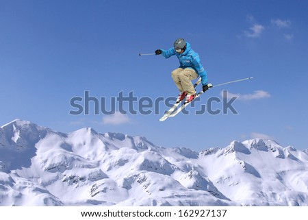 Jumping skier at jump inhigh mountains at sunny day - stock photo
