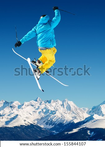 Jumping Skier in high mountains - stock photo