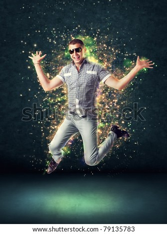 Jumping smiling young man on glowing abstract background - stock photo