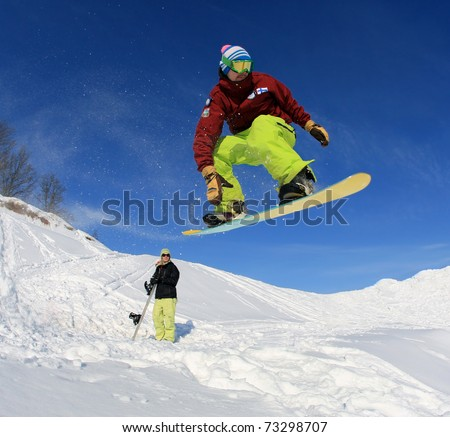 Jumping snowboarder against the blue sky - stock photo
