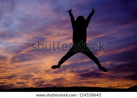 Jumping up into the air at sunset with orange clouds. - stock photo