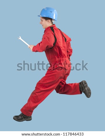 jumping young female manual worker, isolated on blue - stock photo