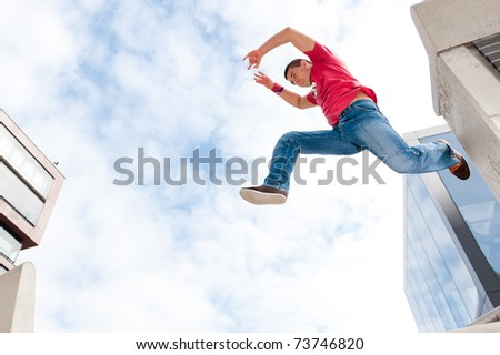 Jumping young man in front of buildings - stock photo