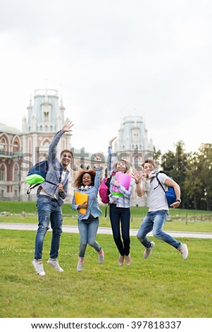 Jumping young student in campus - stock photo