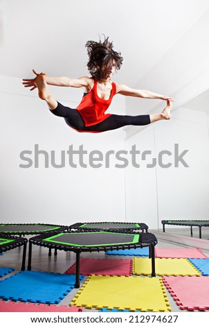 Jumping young woman on a trampoline - stock photo