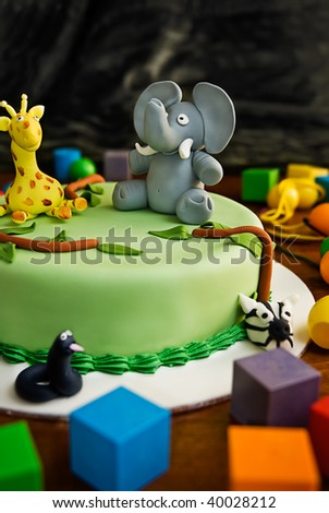 Jungle themed birthday cake with an elephant and giraffe on top, surrounded by building blocks. - stock photo