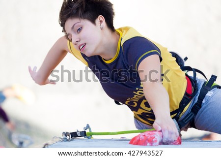 Junior female Athlete makes hard move on climbing Wall of National Competition with very emotional face. Dnipro, Ukraine, May 20, 2016 - stock photo