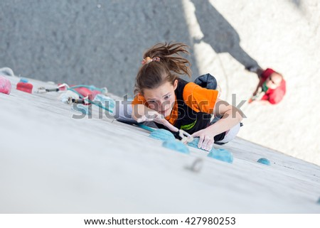Junior female Athlete makes hard move on climbing Wall of National Competition with very emotional face. Dnipro, Ukraine, May 21, 2016 - stock photo