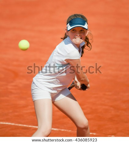 Junior female tennis player about to hit the ball - stock photo