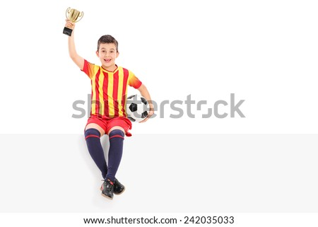 Junior football player holding a trophy on a panel isolated on white background - stock photo
