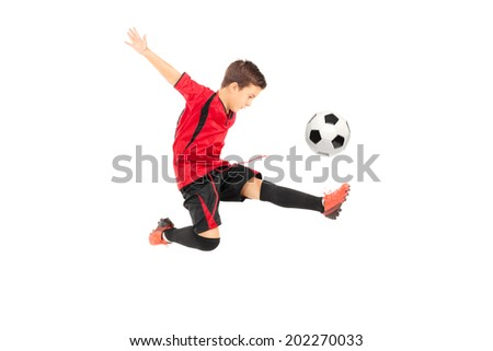 Junior football player kicking a ball isolated on white background - stock photo