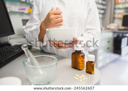 Junior pharmacist mixing a medicine at the hospital pharmacy - stock photo