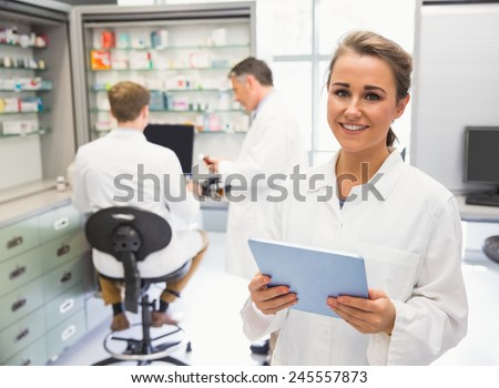 Junior pharmacist using tablet pc at the hospital pharmacy - stock photo