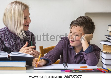 Junior student does homework with the help of his tutor.  - stock photo