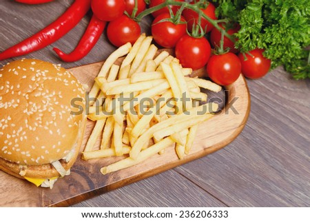 Junk food on a wooden board surrounded by healthy vegetables - stock photo