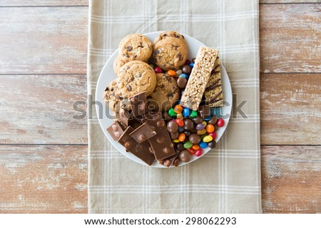 junk food, sweets and unhealthy eating concept - close up of candies, chocolate, muesli and cookies on plate - stock photo