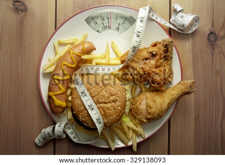 Junk food weighing scales  - stock photo