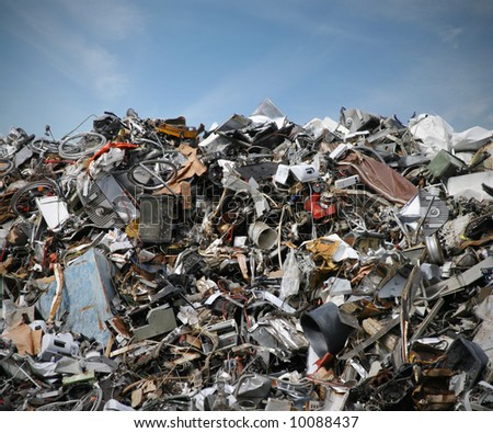 junk yard with old plastic and scrap metal in front of blue sky - stock photo