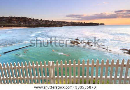 Just after sunrise looking north east across Bronte Baths while people enjoy an early morning swim before work. - stock photo