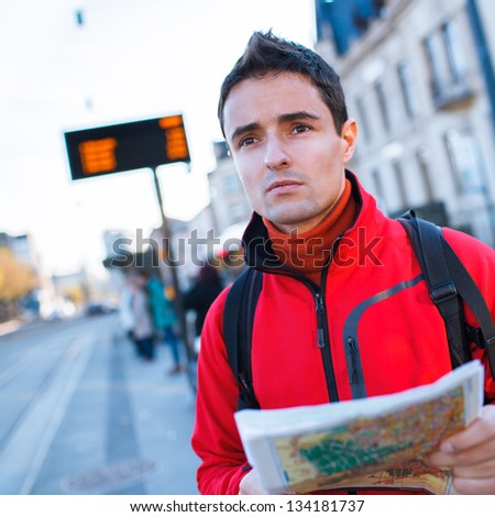 Just arrived: handsome young man studying a map on a bus stop in front of a train station - stock photo