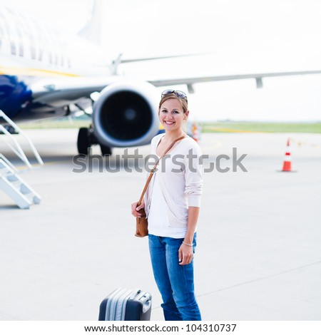 Just arrived: young woman at an airport having just left the aircraft - stock photo