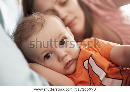 Just Awaken Baby Boy With Mother Lying In Bed - stock photo