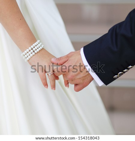 just be with me and never let me go, hands of a young newly wed couple - stock photo