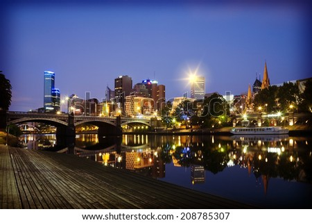 Just before dawn in Melbourne, Victoria, Australia, and the lights of the CBD and Princes Bridge are reflected in the Yarra River, with deep blue sky above, with an instagram filter. - stock photo