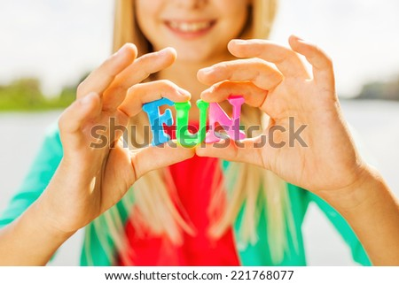 Just for fun! Close-up of cheerful little girl holding colorful plastic letters in her hands and smiling while standing outdoors sun - stock photo