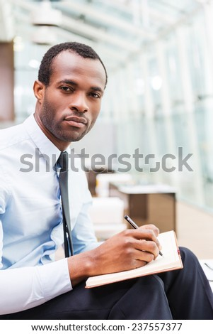 Just inspired. Confident African man in formalwear writing something holding note pad and looking at camera while sitting at his working place - stock photo