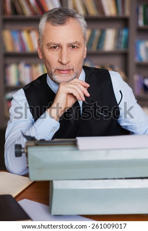 Just inspired. Confident grey hair senior man in formalwear sitting at the typewriter and looking at camera with bookshelf in the background - stock photo