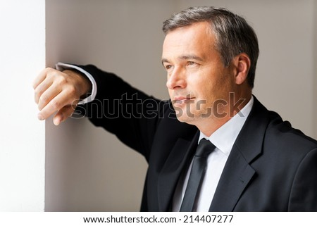 Just inspired. Thoughtful mature man in formalwear looking away while leaning at the wall - stock photo
