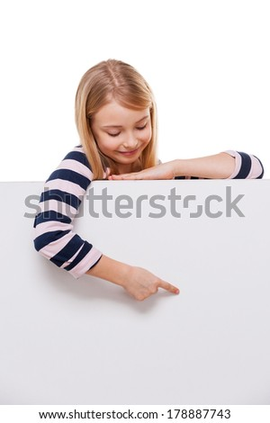 Just look at that! Cheerful little girl leaning at copy space and pointing it while isolated on white - stock photo