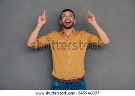 Just look at that! Happy mature man pointing up while standing against grey background - stock photo