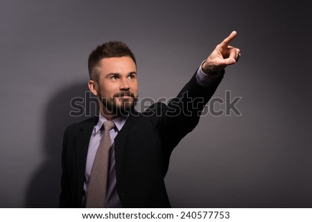 Just look at that! Happy young man in formalwear pointing away and smiling while standing against grey background  - stock photo