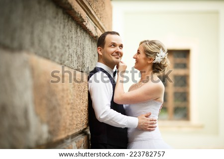 Just married couple embrace, wedding pair hugging, Bride and Groom, Romantic Married Couple posing near the wall and play, beautiful couple smiling to the camera, They Hug each other, wedding - stock photo