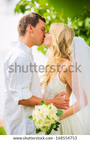 Just married couple kissing and embracing, Intimate loving moment at wedding - stock photo