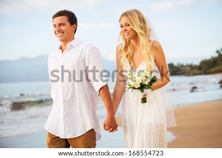 Just married couple on walking on the beach at sunset, Hawaii Beach Wedding - stock photo