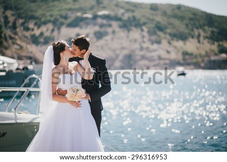 Just married couple posing in small cove. Happy bride and groom on their wedding day - stock photo