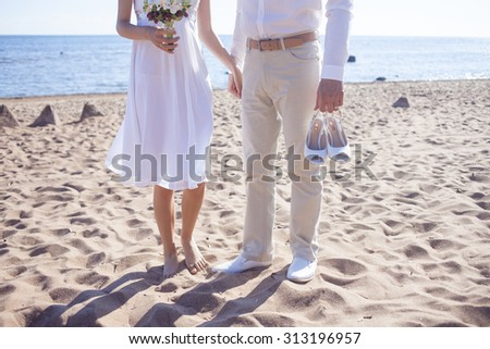 Just married couple running on a sandy beach,  feet  view, groom holds shoes - stock photo